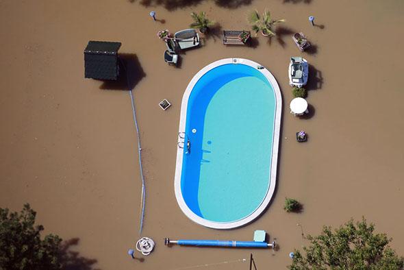 Um jardim com uma piscina é inundada pelas águas do rio Elbe durante as inundações perto de Magdeburg no estado federal da Saxônia-Anhalt, 10 de junho de 2013.