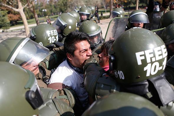 Um estudante manifestante morde um policial ao ser detido durante um motim em uma manifestação exigindo a reforma do sistema de educação do governo Chileno  em Santiago, 08 de maio de 2013.