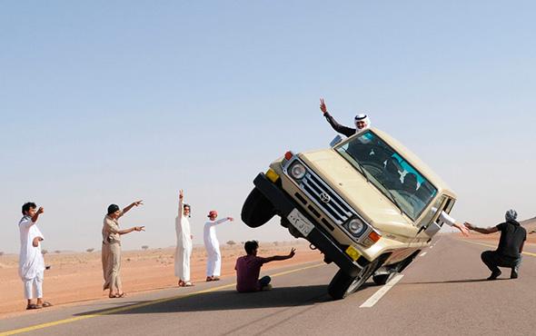 """Jovens sauditas demonstram um truque conhecido como """"esqui lateral"""" (dirigir em duas rodas) no norte da cidade de Hail, na Arábia Saudita, 30 de março de 2013."""