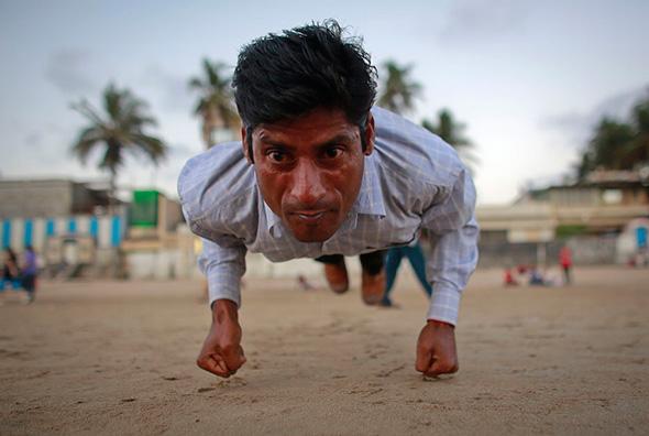 Ram Pratap Verma, um  aspirante a ator de cinema de Bollywood de 32 anos, pratica ginástica em uma praia em Mumbai, 17 abril de 2013.