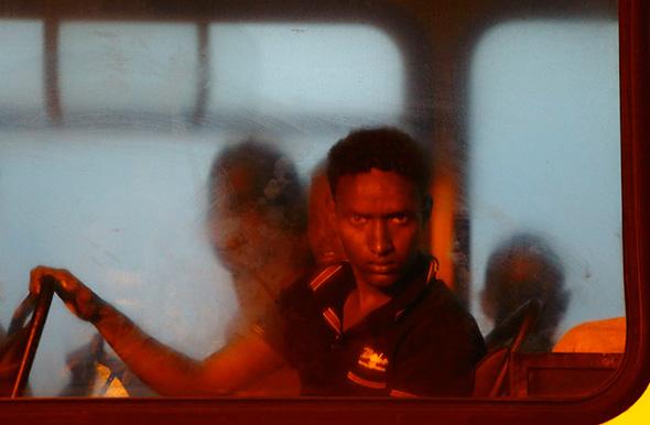 Um pretenso imigrante olha para fora de uma janela em um ônibus da polícia depois de chegar às Forças Armadas de Malta (AFM)  em  Haywharf em Valletta de Marsamxett Harbour início de 10 de julho de 2013.
