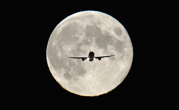 """Um avião de passageiros, em plena a """"Harvest Moon"""" visto por trás, faz sua aproximação final para pouso no aeroporto de Heathrow no oeste de Londres, 19 de setembro de 2013."""