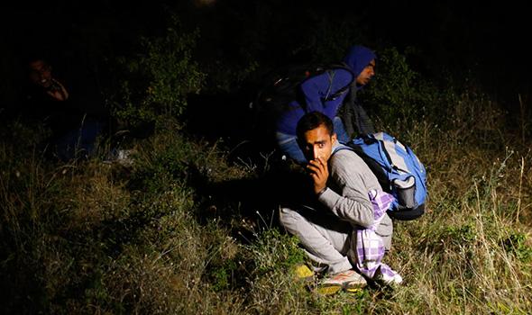 Imigrantes, que disseram que eram da Síria, sentam no chão depois de terem sido detidos pela polícia na fronteira com a Sérvia, porque entraram ilegalmente no país da Macedônia, perto da cidade de Presevo alguns 383 km (238 milhas) da capital de Belgrado 17 de julho de 2013.
