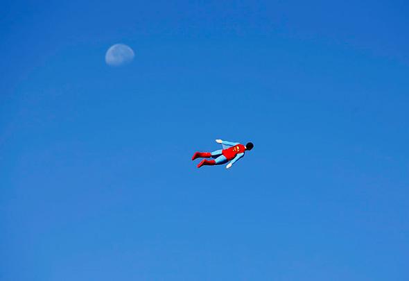 Um avião de Superman controlado por rádio e pilotado pelo designer Otto Dieffenbach, passa perto da lua durante um vôo de teste em San Diego, Califórnia, 27 de Junho de 2013.