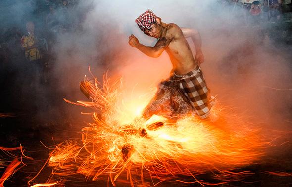 """Um homem chuta para cima o fogo durante o ritual """"Perang Api"""" antes do dia da Nyepi,  em Gianyar na ilha indonésia de Bali, 11 de março de 2013"""