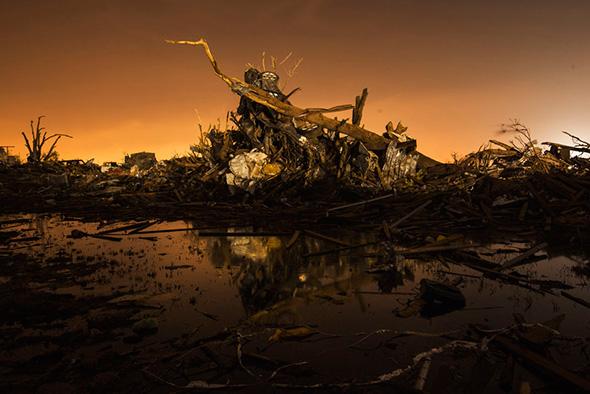 Um carro fica em cima de uma pilha de detritos empurrado pelo vento em uma área fortemente danificada pelo tornado de 20 de maio em Moore, Oklahoma, 27 maio de 2013.