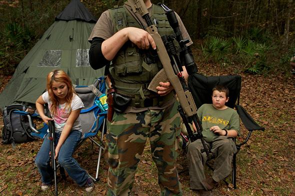 Os membros do Grupo de Sobrevivência do Norte da Florida , esperam com seus rifles antes de sair para executar treinos de contato inimigo durante um exercício de treinamento de campo em Old Town, Florida, 08 de dezembro de 2012.