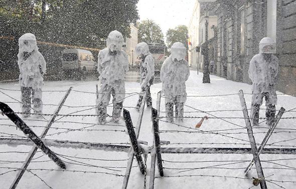 A Polícia de choque belga são cobertas com espuma pulverizada pelos bombeiros durante um protesto por melhores condições de trabalho no centro de Bruxelas 07 de outubro de 2013.