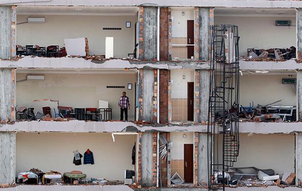 Um homem verifica um apartamento em um edifício danificado no local de uma explosão na cidade de Reyhanli, na província de Hatay, perto da fronteira turco-síria, 13 de maio de 2013.