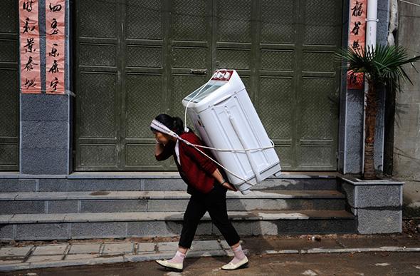 Uma mulher carrega para casa uma máquina de lavar roupa em Dali, província de Yunnan, 30 de julho de 2013.
