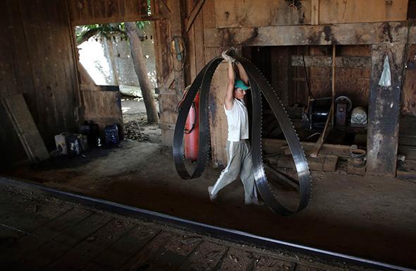 Um trabalhador carrega uma lâmina em uma serraria que processa árvores ilegalmente na selva amazônica, perto da cidade de Morais Almeida, Estado do Pará, 27 de junho de 2013.
