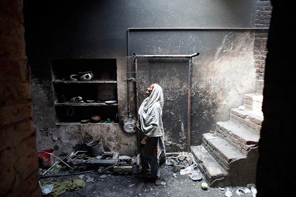 Azra, de 68 anos, olha para o seu pássaro de estimação morto em uma gaiola em sua casa, que foi queimada por uma multidão, dois dias antes, em Badami Bagh, Lahore 11 de março de 2013.