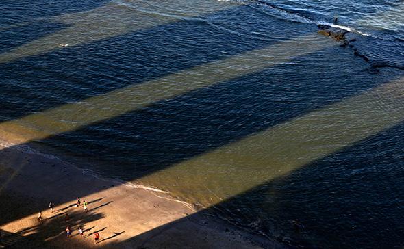 Homens jogam futebol entre as sombras de edifícios na Praia da Boa Viagem, em Recife 14 de junho de 2013.