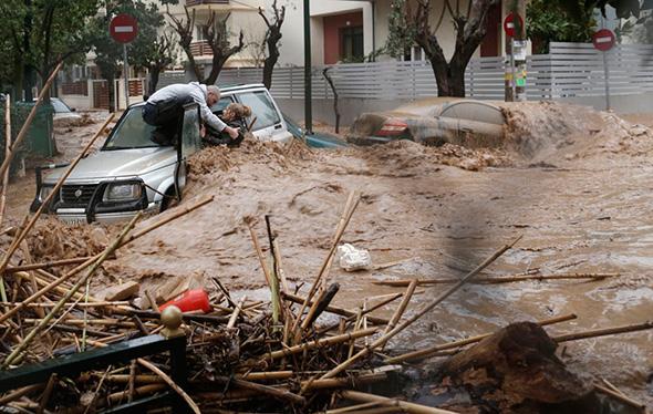 Uma mulher é resgatada de águas da inundação por um homem em cima de seu carro durante uma chuva forte em Chalandri, subúrbio norte de Atenas -  22 de fevereiro de 2013.