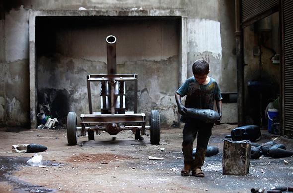 Issa, 10 anos, carrega um morteiro em uma fábrica de armas do Exército Livre da Síria em Aleppo, 7 de setembro de 2013. Issa trabalha com seu pai na fábrica durante dez horas todos os dias, exceto às sextas-feiras.