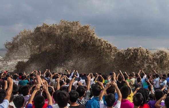 Os visitantes aproveitam para tirar fotos de um maremoto sob a influência do tufão Usagi em Hangzhou, província de Zhejiang, 22 de setembro de 2013.