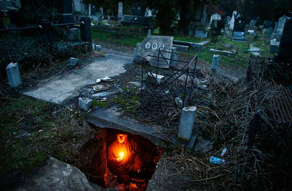 Bratislav Stojanovic, um sem-teto, acende velas enquanto se senta em uma tumba onde ele vive na cidade meridional sérvia, 9 de fevereiro de 2013.