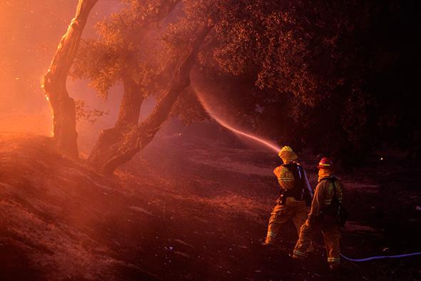 Bombeiros jogam água perto de uma casa em chamas na área de Twin Pines, perto de Banning, Califórnia, 7 de agosto de 2013.
